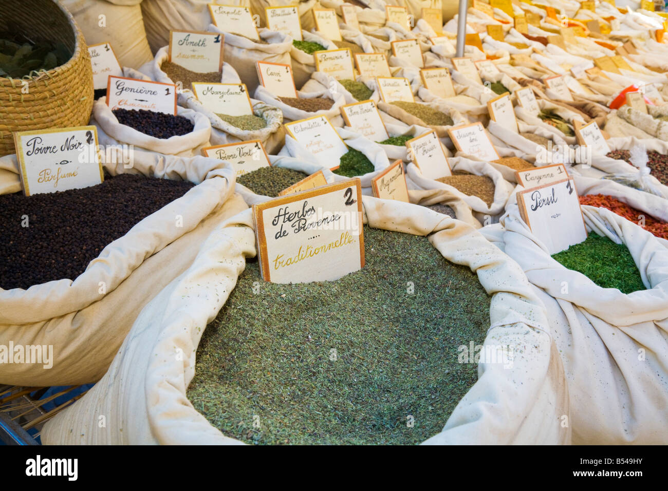 A variety of herbs and spices (provençal herbs in the foreground) is being offered at a farmers market in the - Stock Image