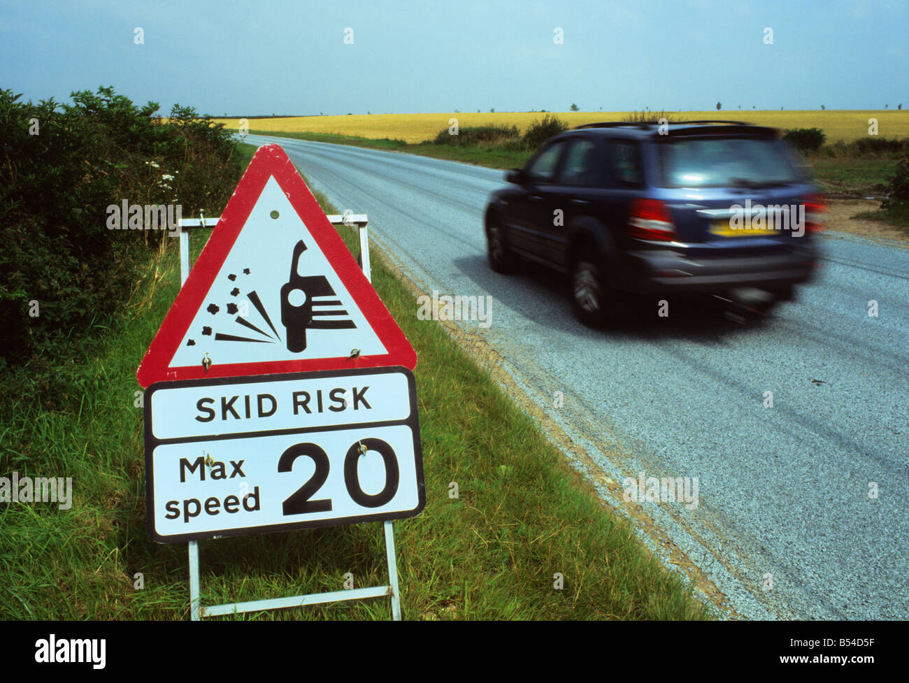 four by four vehicle passing warning sign of slippery road surface on newly resurfaced road near Leeds Yorkshire Stock Photo