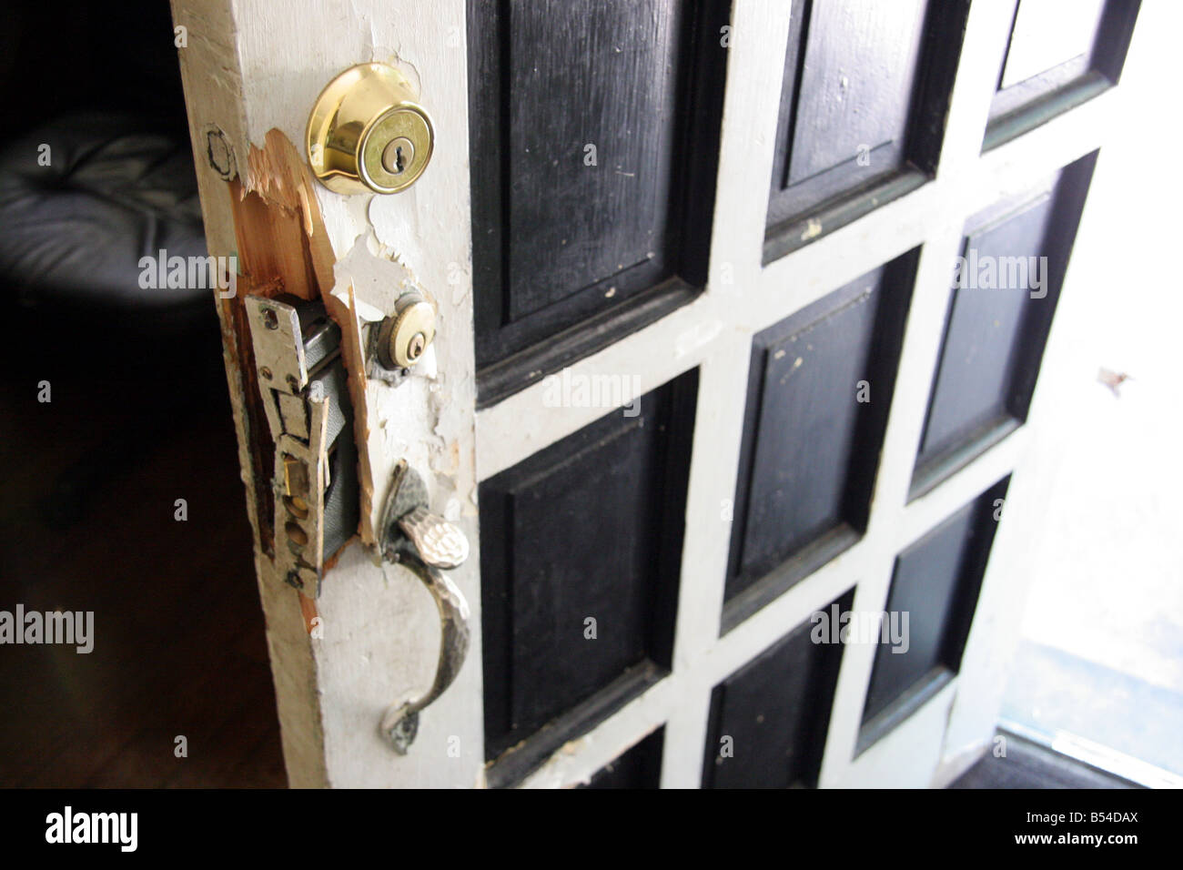 Broken door and lock damaged by police during a drugs raid in Detroit Michigan USA & Broken door and lock damaged by police during a drugs raid in ...
