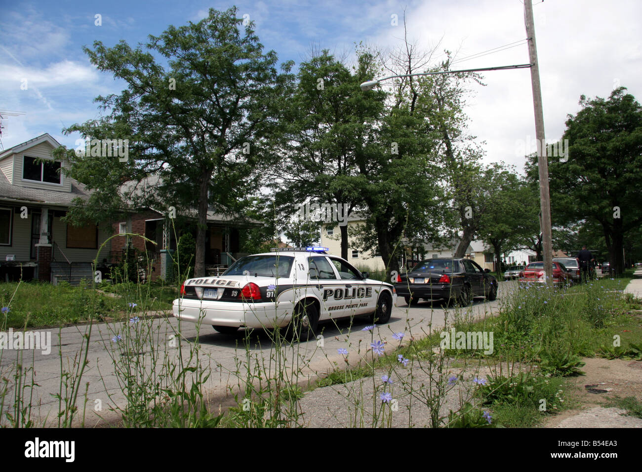 Grosse Pointe Park police car conducting a traffic stop in a poor neighbourhood of Detroit Michigan - Stock Image