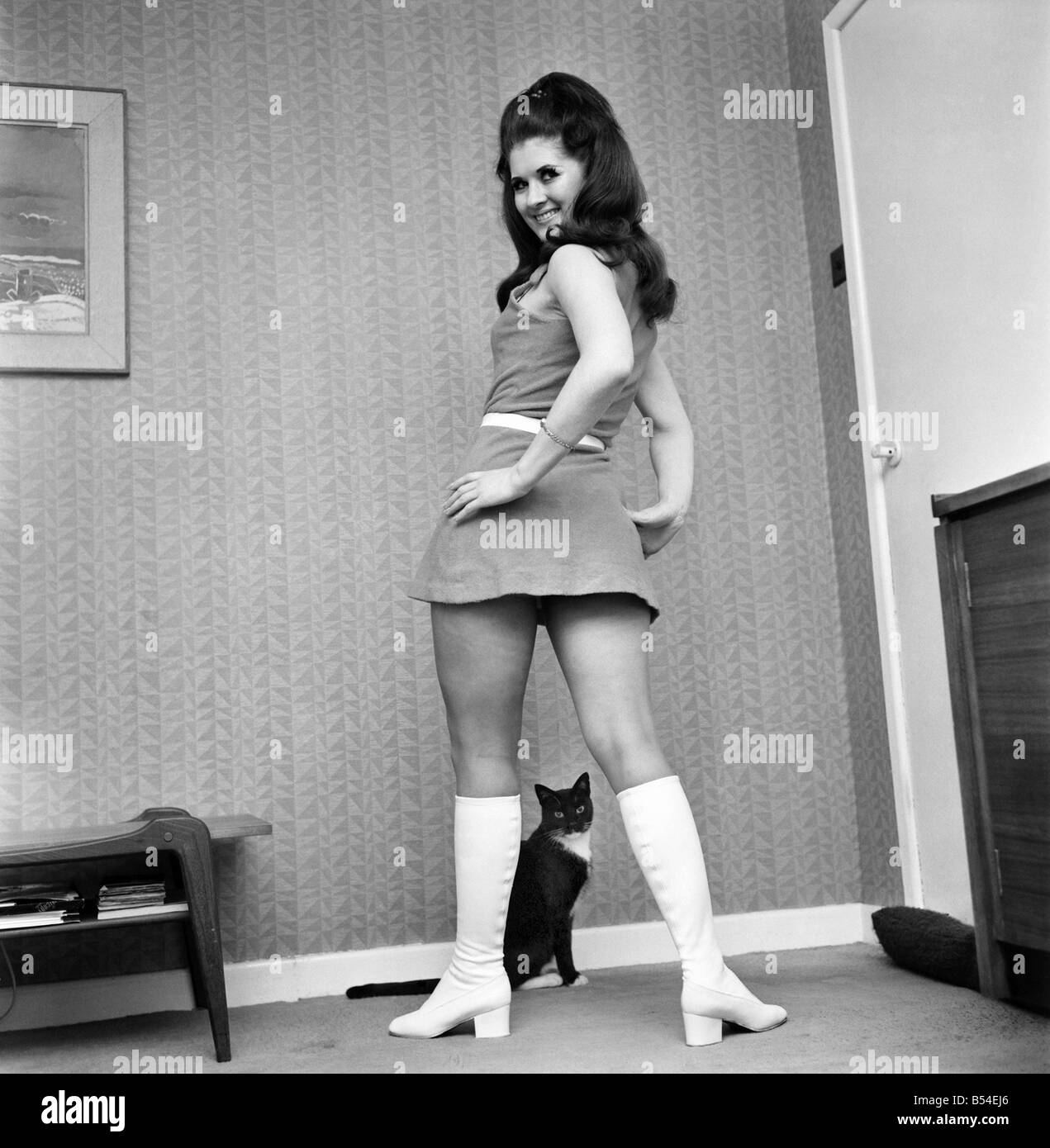 Fashion Clothing: A woman posing in her home weaving a mini dress and white knee high boots. November 1969 Z10905 Stock Photo