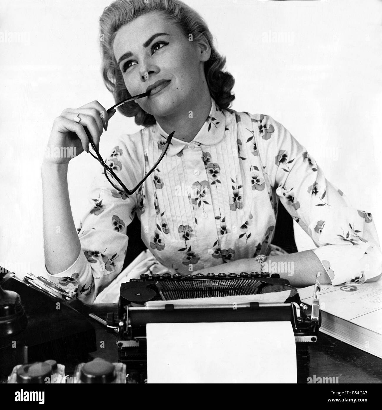 Secretary at typewriter chewing the end of her glasses daydreaming Typist spectacles Office worker W.S.M. Features - Stock Image