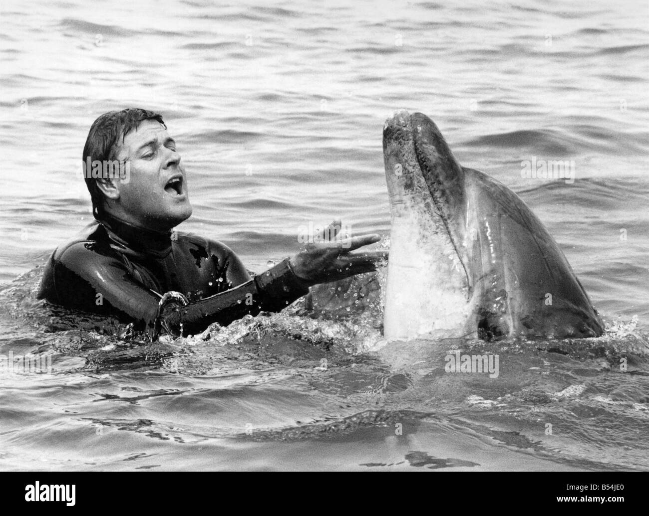 Lakeman and Percy the dolphin frolic together. July 1984 P011844 - Stock Image