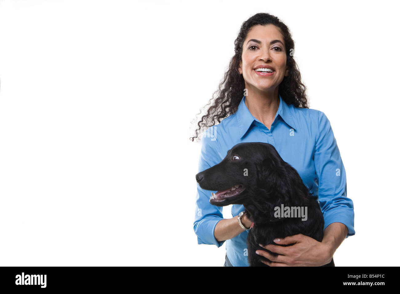 woman plays with one black dog on white background - Stock Image