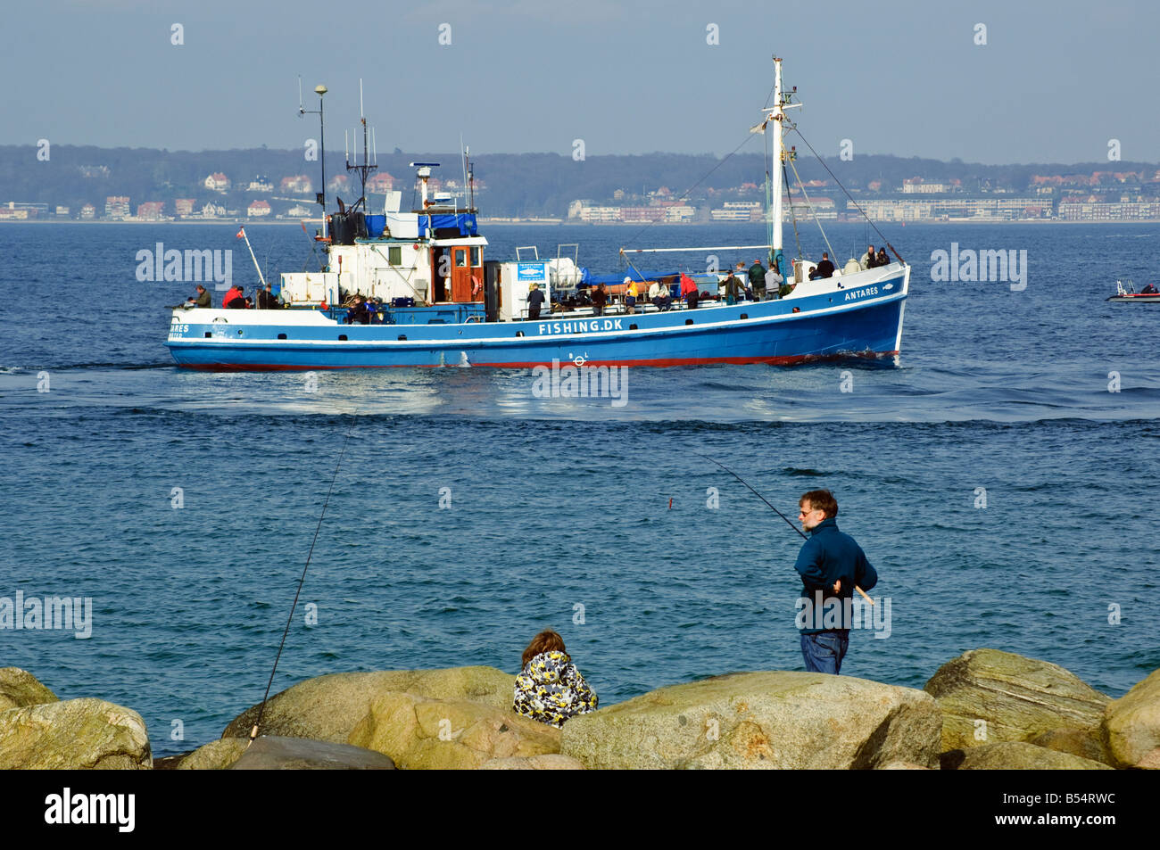 Anglers and fishing boat Helsingør Denmark looking across the Öresund strait to Helsingborg in Sweden - Stock Image
