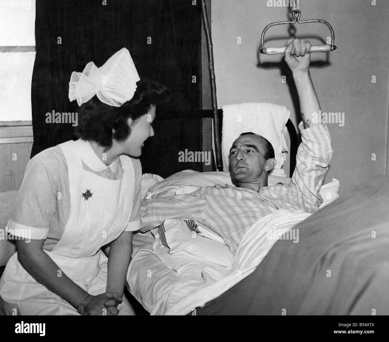 World War II: Hospitals. L/Cpl. Harold Evans pulling himself up on the balkan beam in the same way as he did when - Stock Image