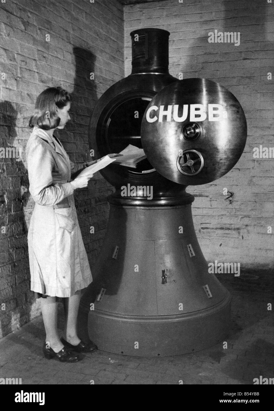 The 2 1/2 ton Revolving Lighthouse Safe. Here a woman is seen placing papers in the lighthouse. She is also locking - Stock Image