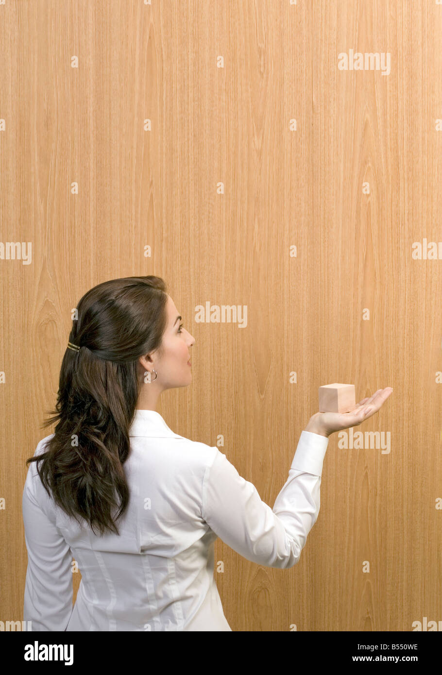 woman holds wooden cube - Stock Image