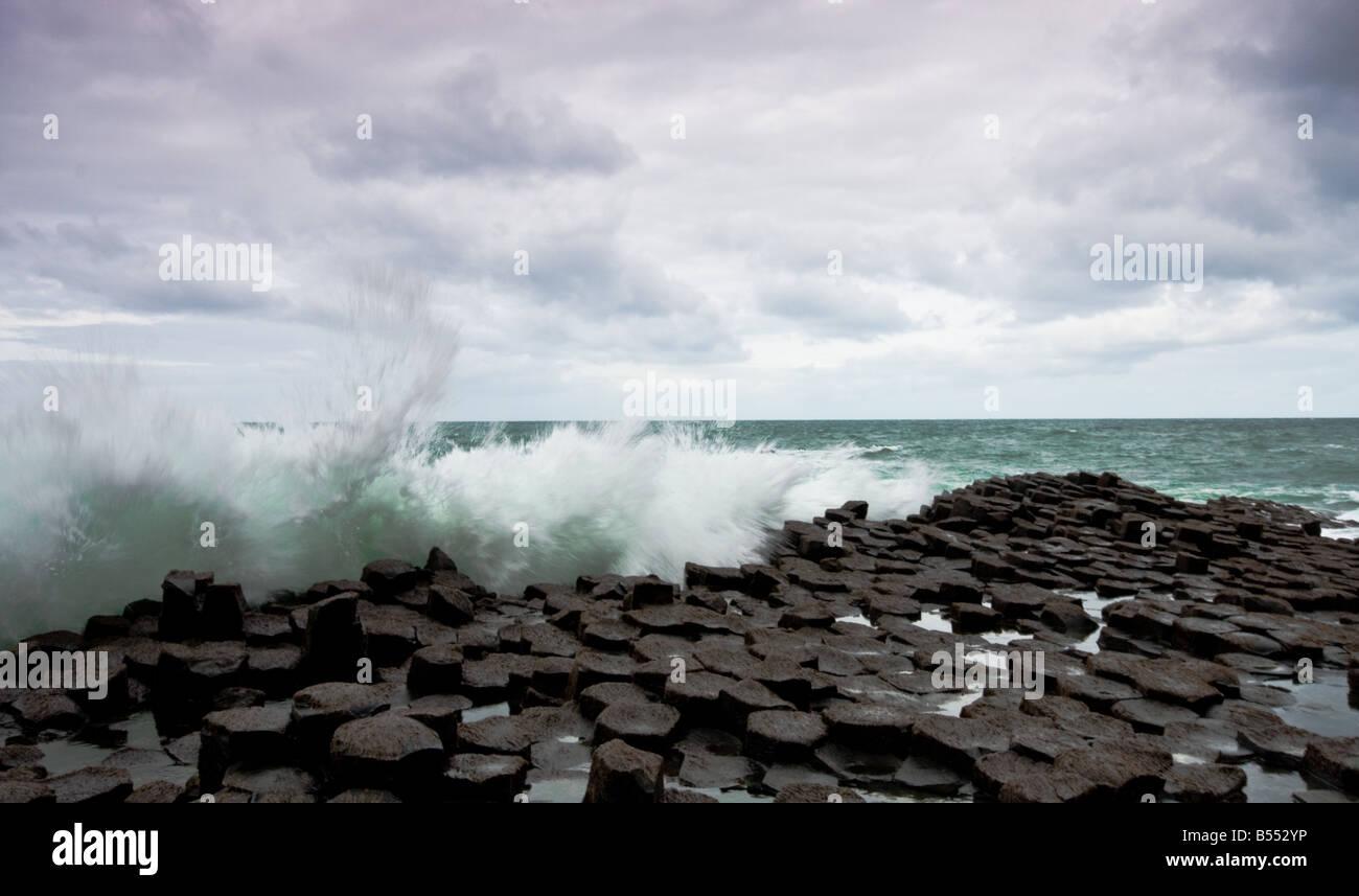 Waves crashing over the giants causeway, ireland - Stock Image
