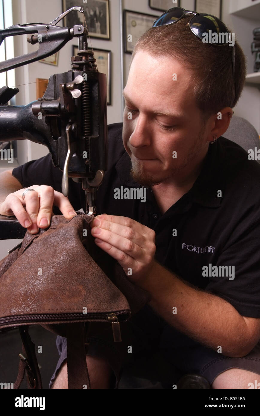A man uses an antique Singer sewing machine to repair leather goods in a small shop in Maryland USA - Stock Image