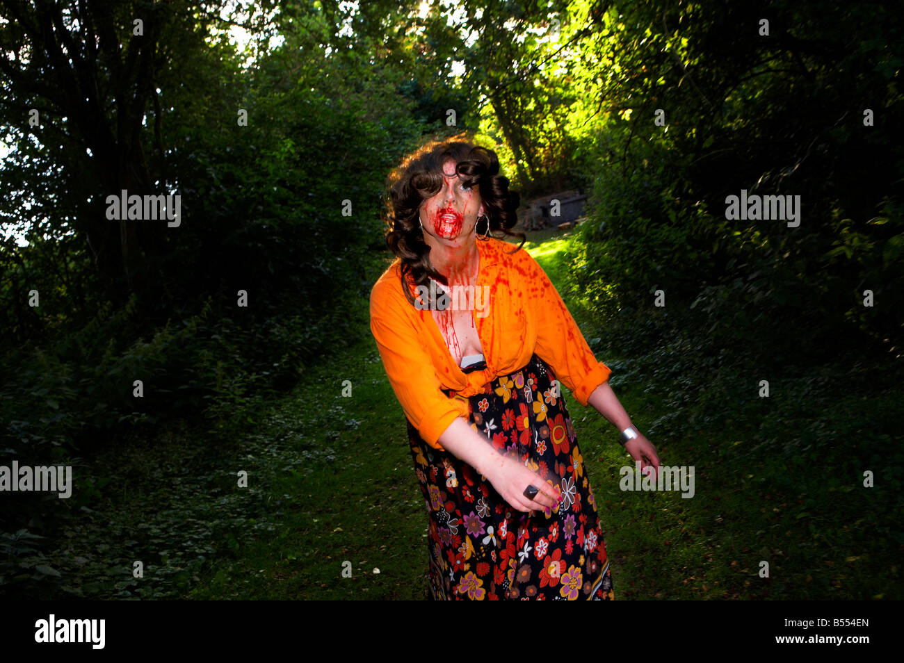 A woman dressed as a zombie walks through the woods - Stock Image