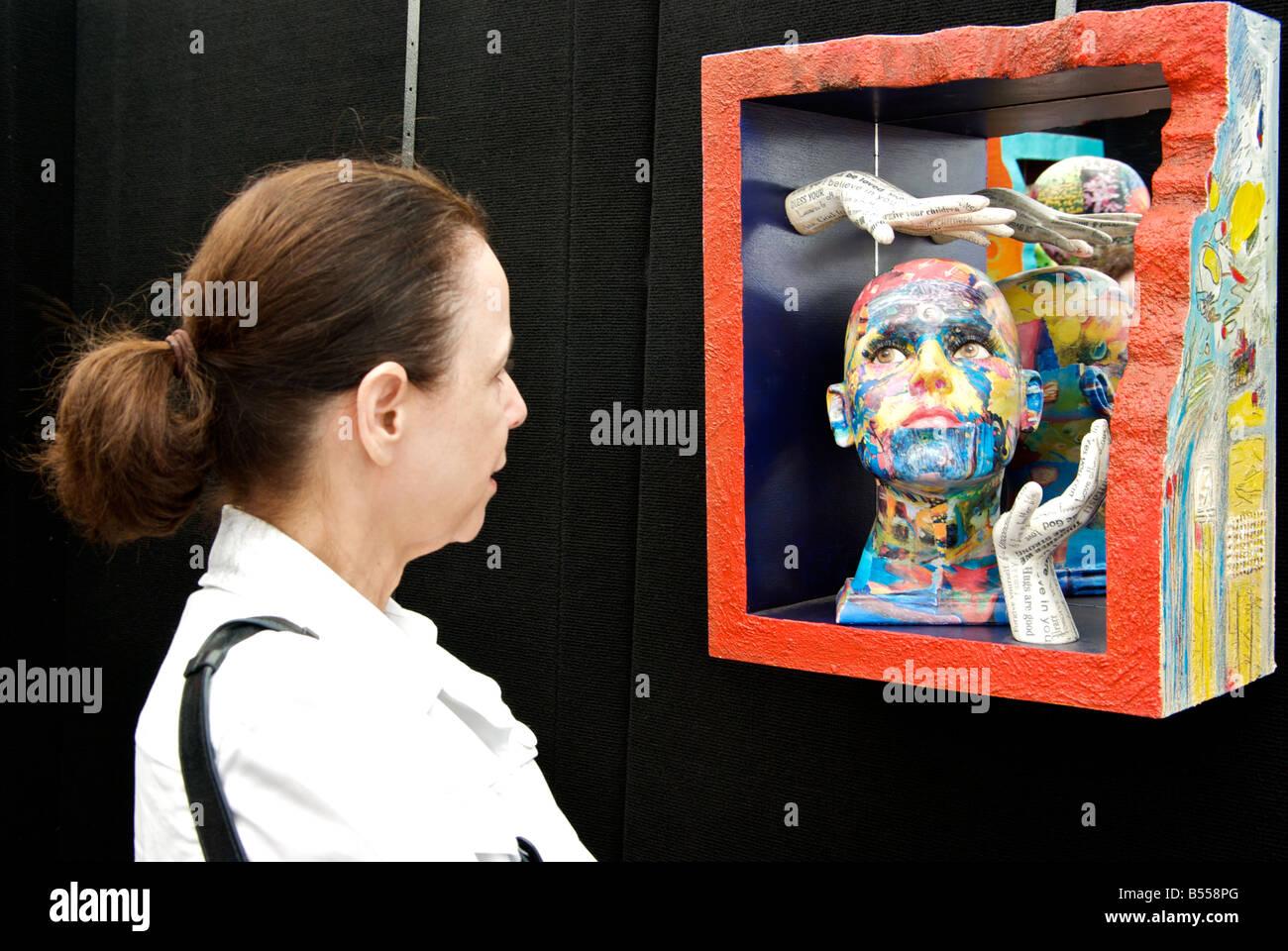 Woman at Bayou City Art Festival in Houston Texas looking at Sheryl McDonald 3 D mixed media mannequin art exhibit - Stock Image