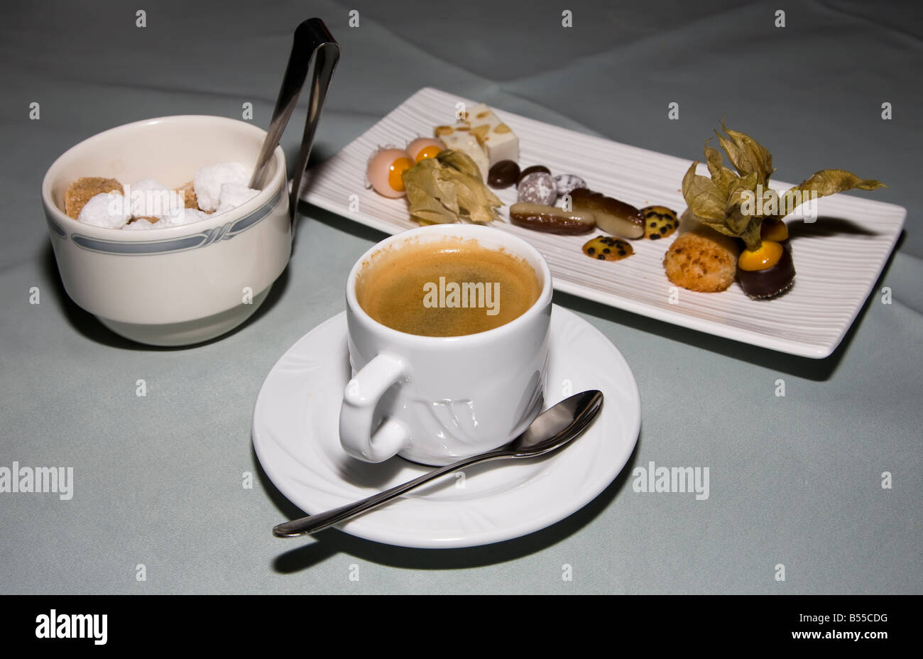 Black coffee with sugar lumps in bowl with tongs and sweets on table Belgium - Stock Image