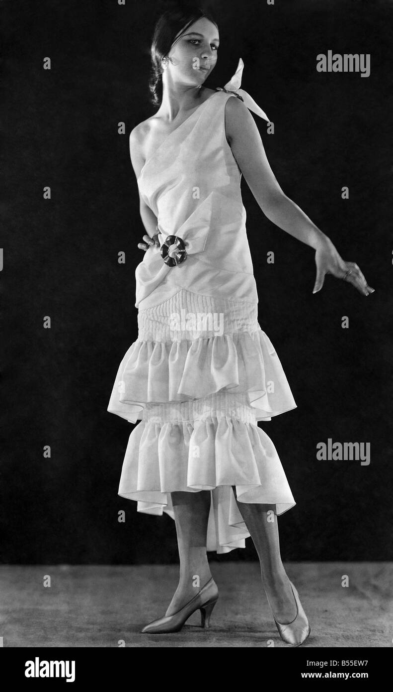 A modern gown reminiscent of the eighties in ivory faille with buckles of jade and diamante. ;May 1929 ;P008649 - Stock Image