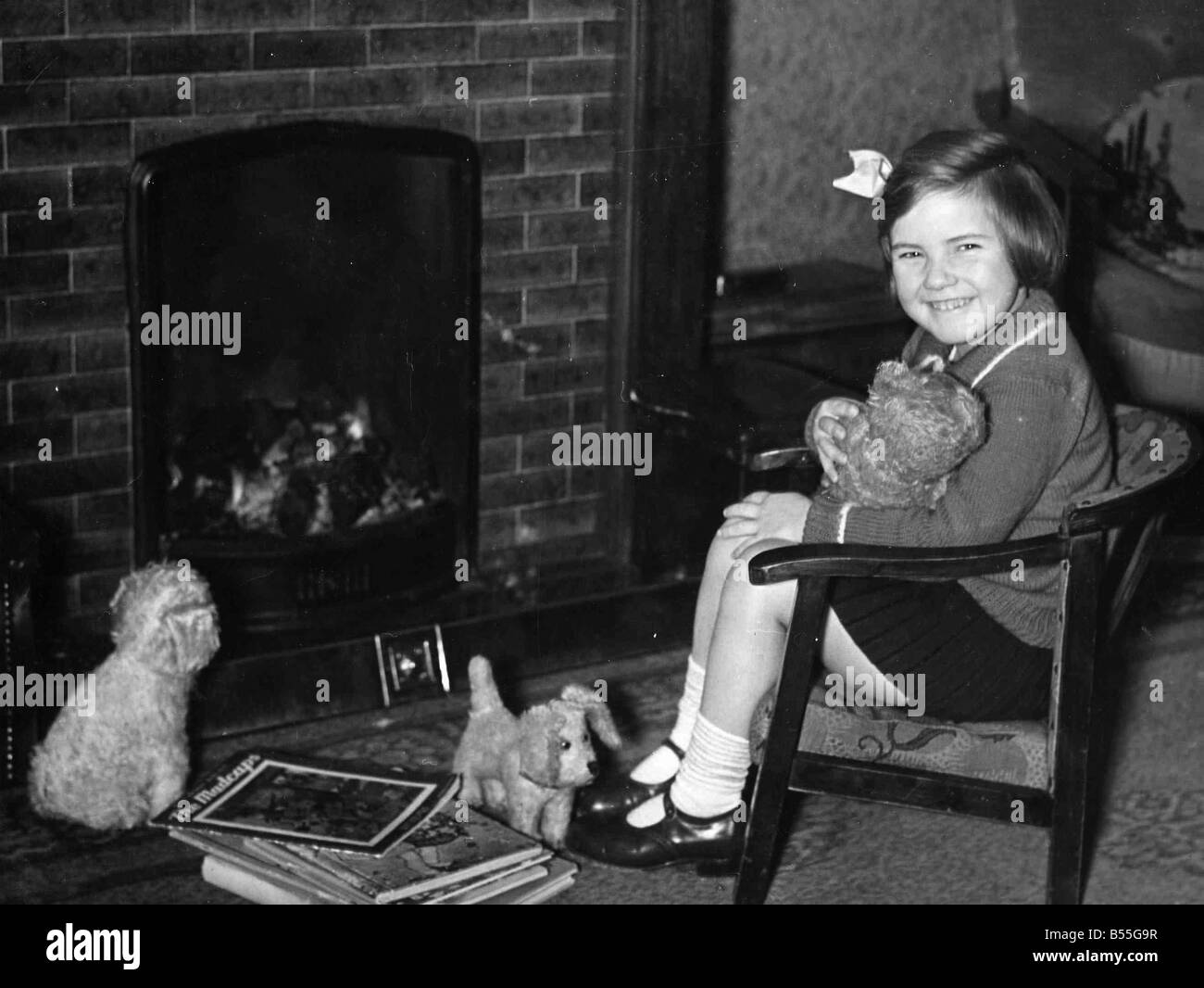 Young girl sitting by fireplace with toy dogs. c.1945P044479 - Stock Image