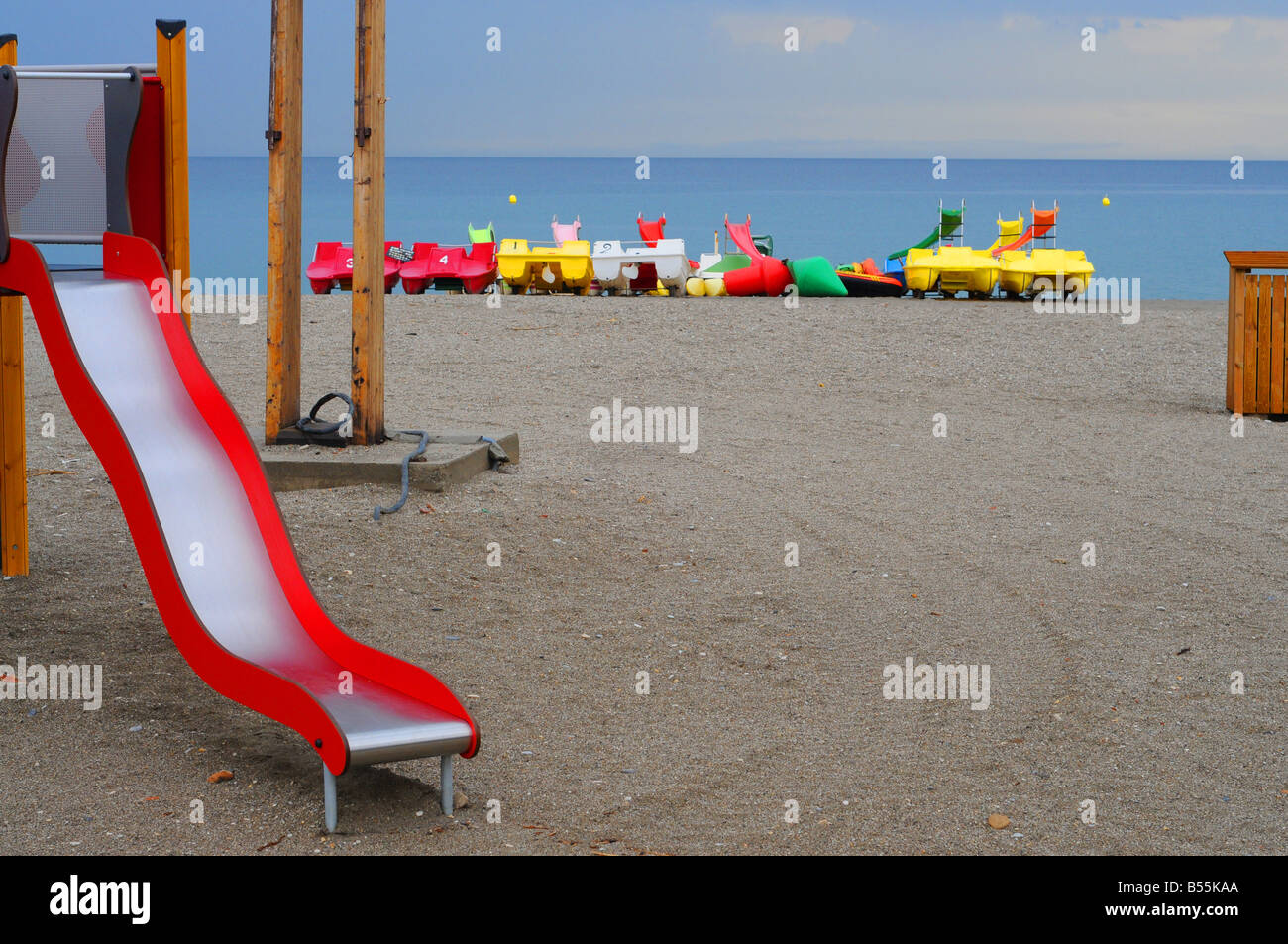 A children's slide on a deserted beach in southern Spain, out of season, with pedalo pedal boats in the background. - Stock Image