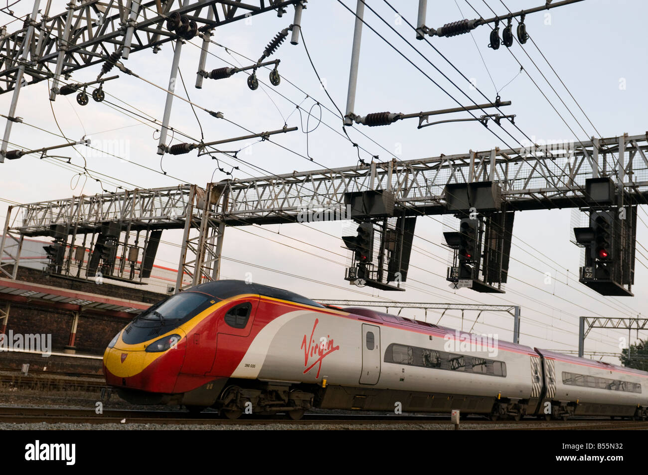 A Virgin Trains pendolino inter-city train arriving  at running on the West Coast main line arriving AT Crewe Railway - Stock Image