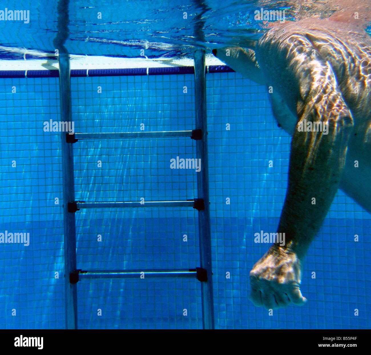 man swimming near pool exit ladder - Stock Image