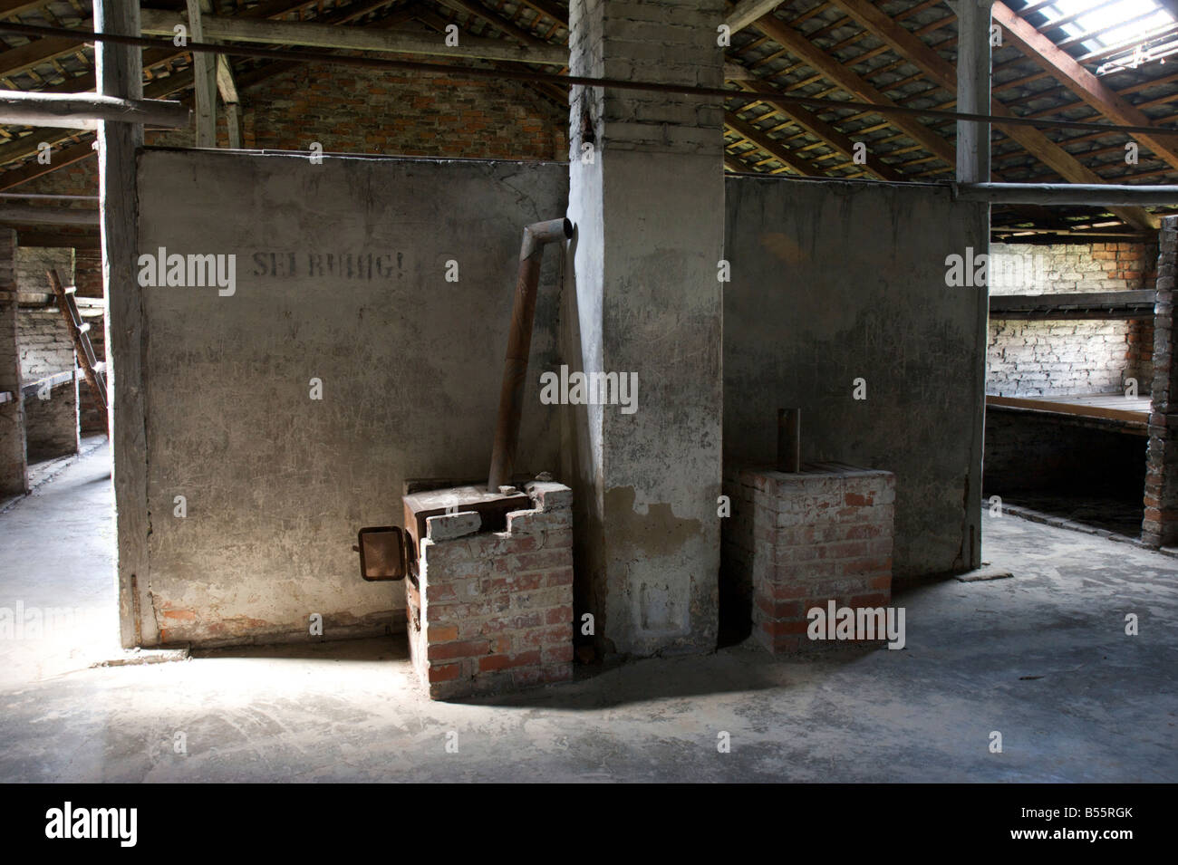 Brick heating ovens inside of a prisoners sleeping barrack in former concentration camp Auschwitz II (Birkenau) - Stock Image
