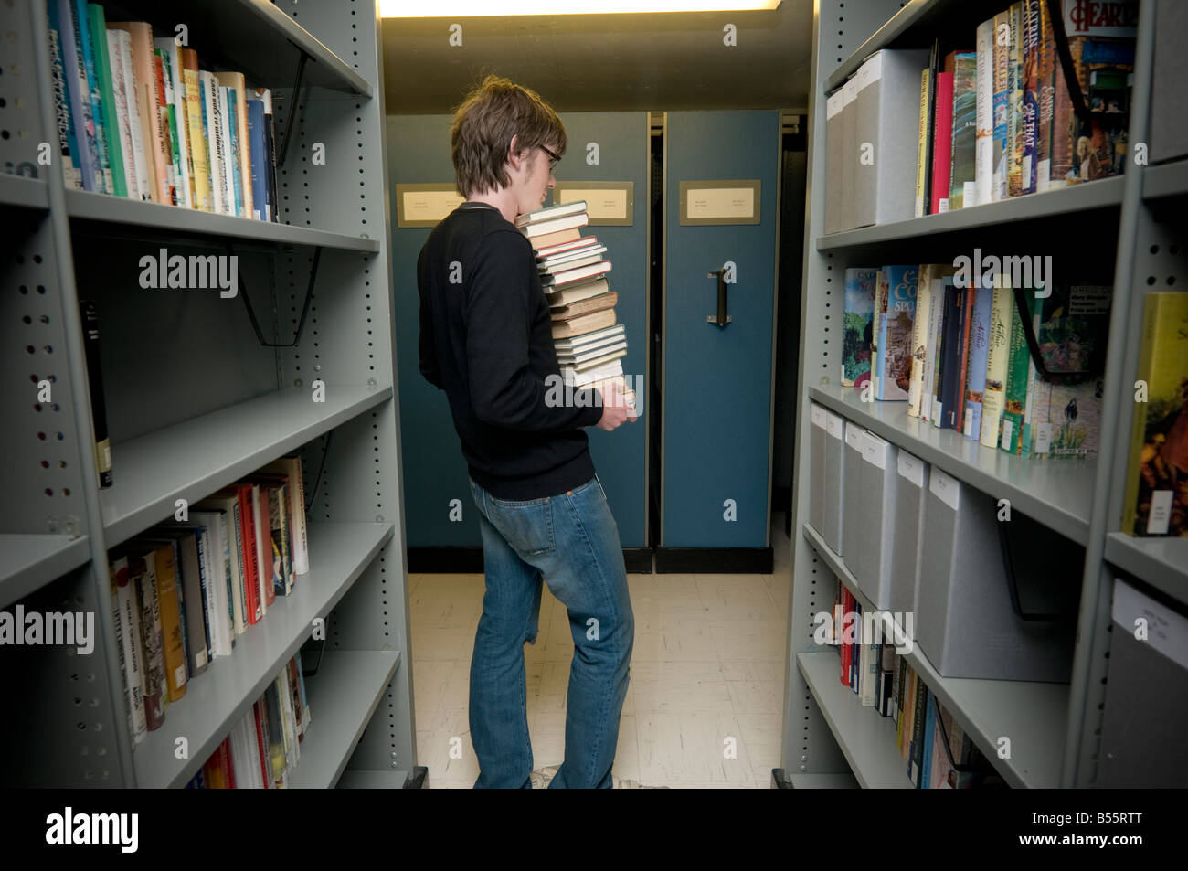 Man collecting books from the archives of the National Library of Wales Aberystwyth to take them to be scanned and - Stock Image