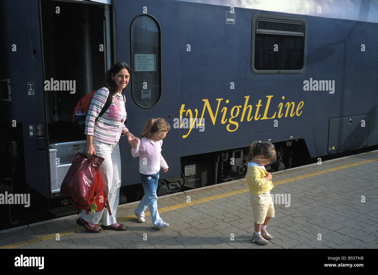 Mother and children leave a city nightline sleeper train in Vienna Austria - Stock Image