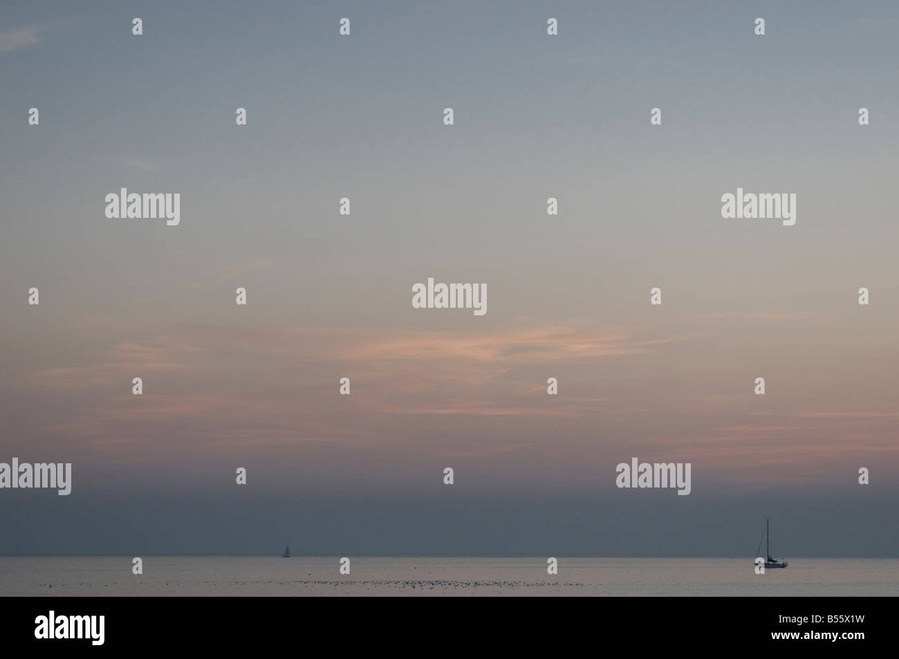 Dusk over Cardigan Bay west wales yachts on the flat calm sea, UK Stock Photo