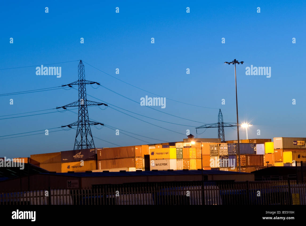 A view of large storage containers at sunrise lit up by spot lights with electricity pylons silhouetted in the background - Stock Image