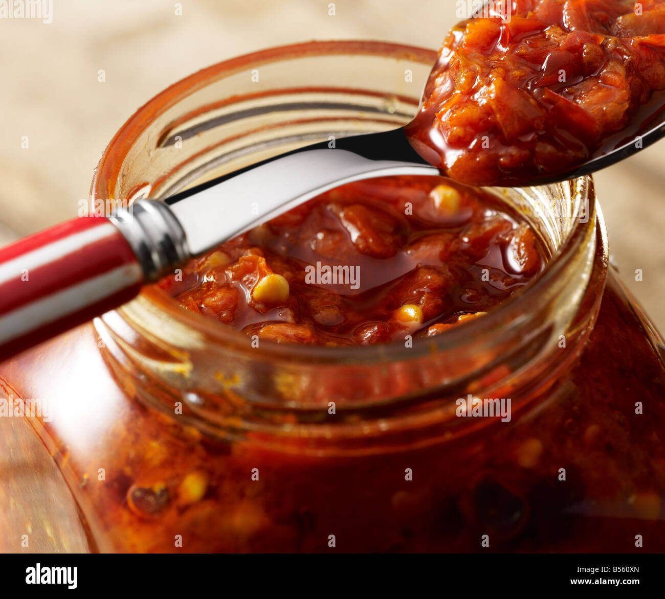 A spoon on a jar of hot Chilli sauce - Stock Image