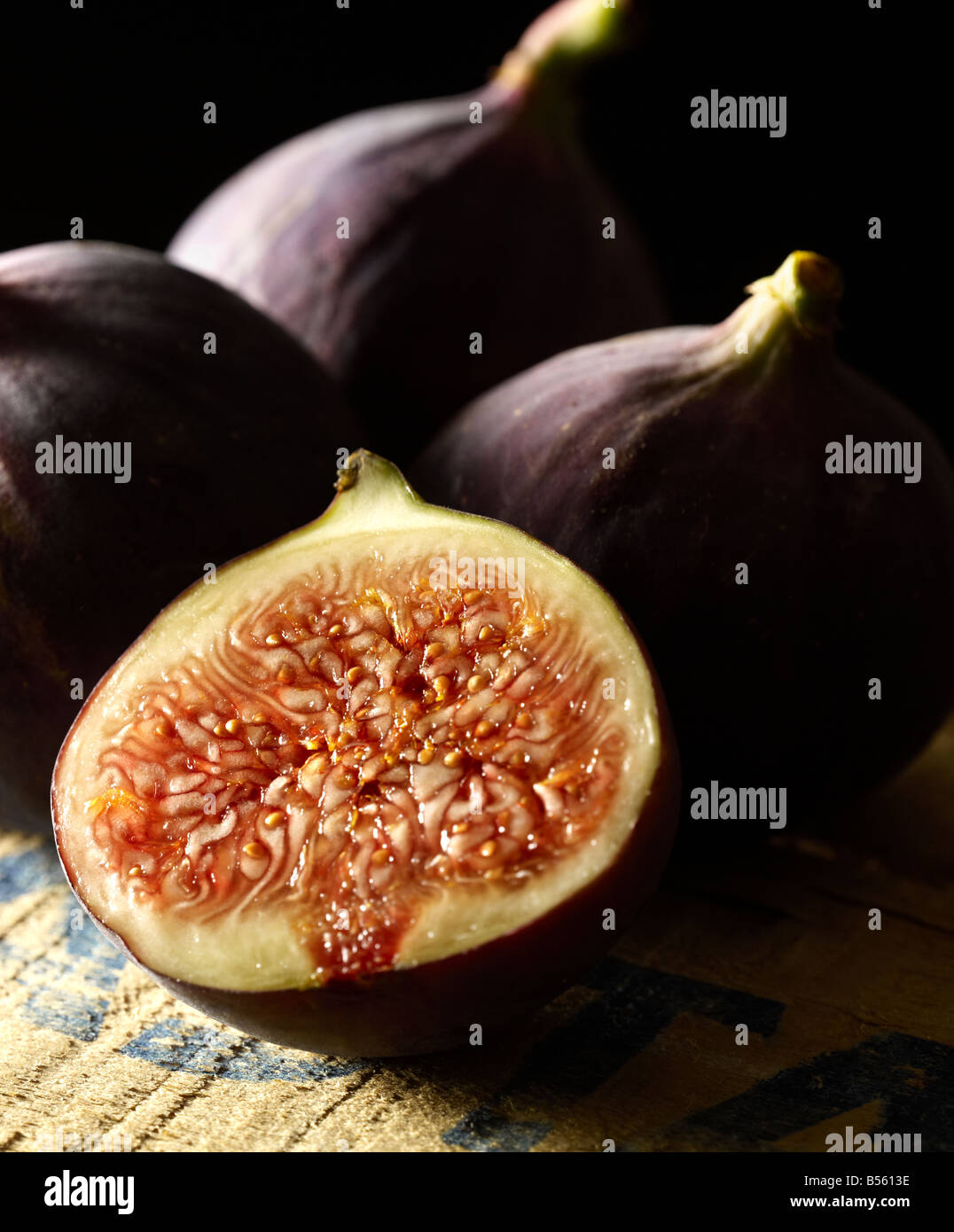 Fresh purple Figs one cut open to show the seeds - Stock Image