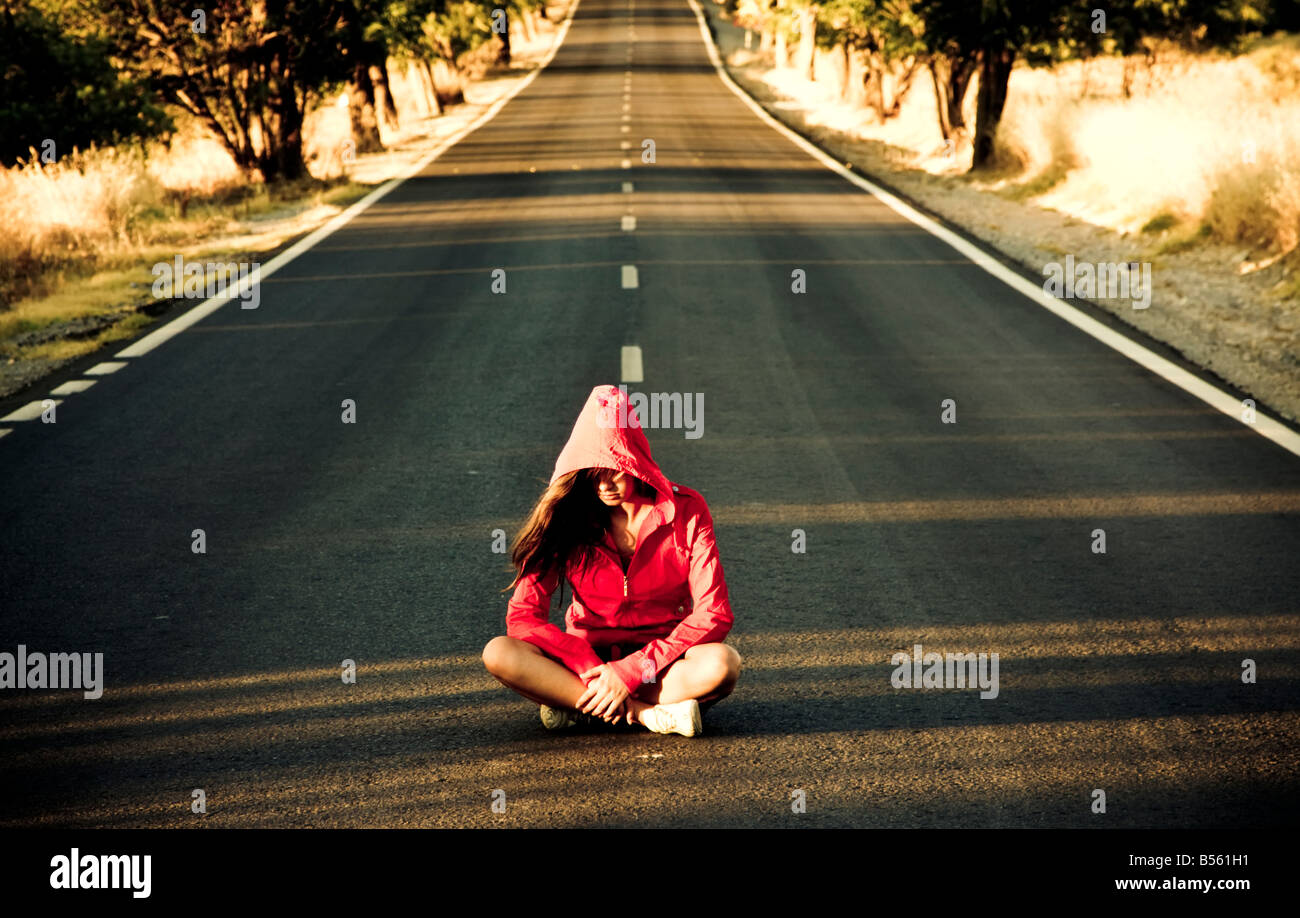 Unrecognizable mystery woman in the middle of the road - Stock Image