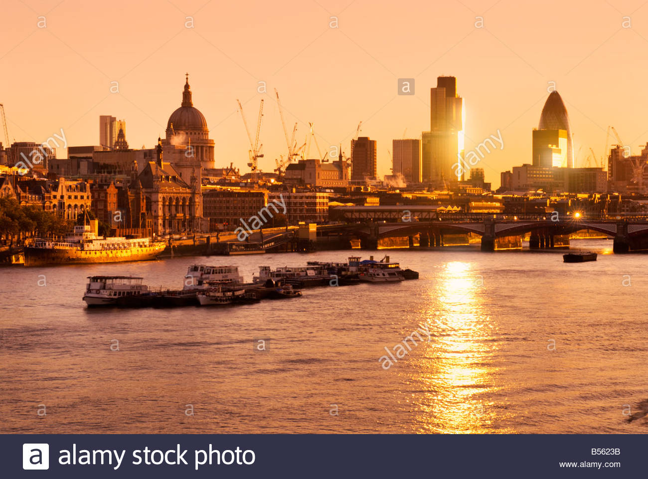 The River Thames and the city skyline at sunrise London UK - Stock Image
