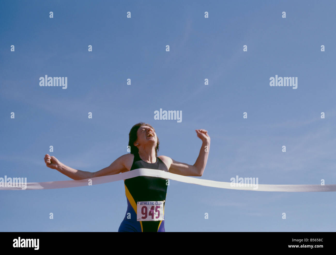 Women victoriously crossing the finish line of track race Stock Photo