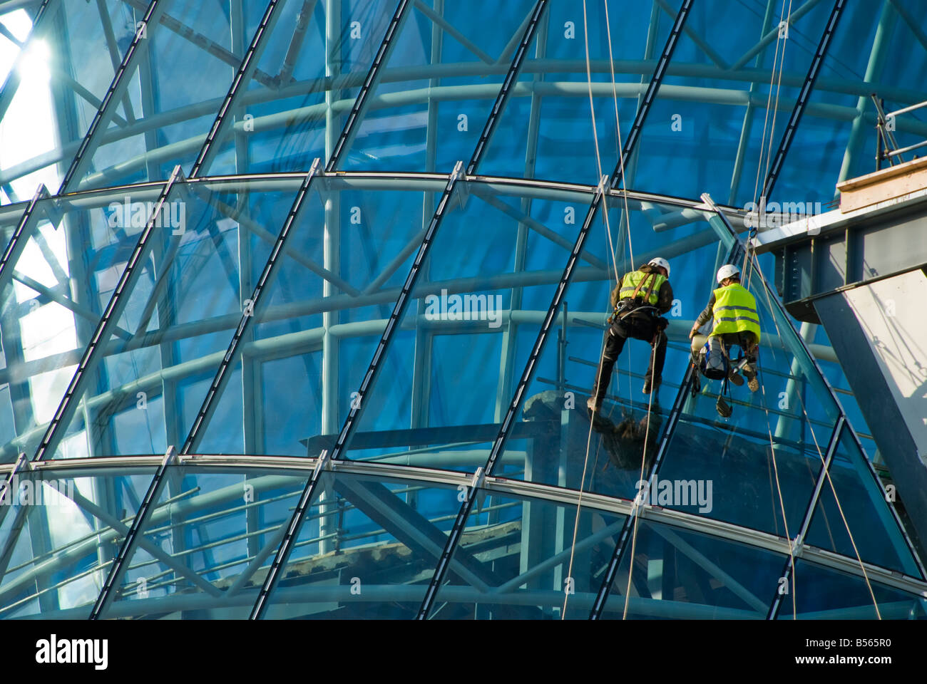 Teams of construction engineers working on the glazing of the new National Conference Center on North Wall Quay - Stock Image