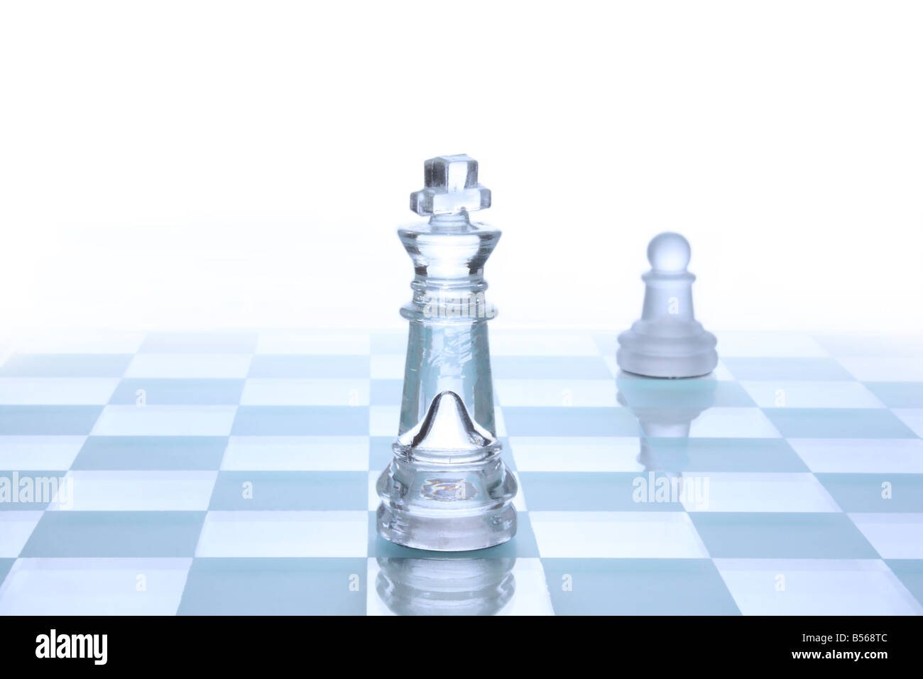 Translucent glass chess figures on a board - Stock Image