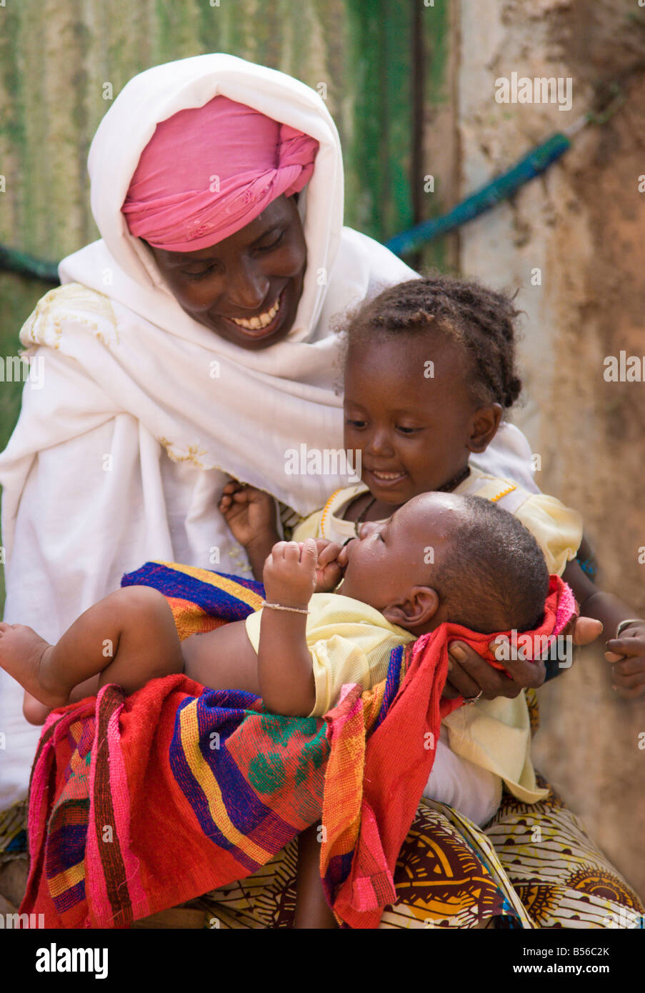 A Fulani woman in Ouagadougou Burkina Faso holds her two youngest children on her lap - Stock Image