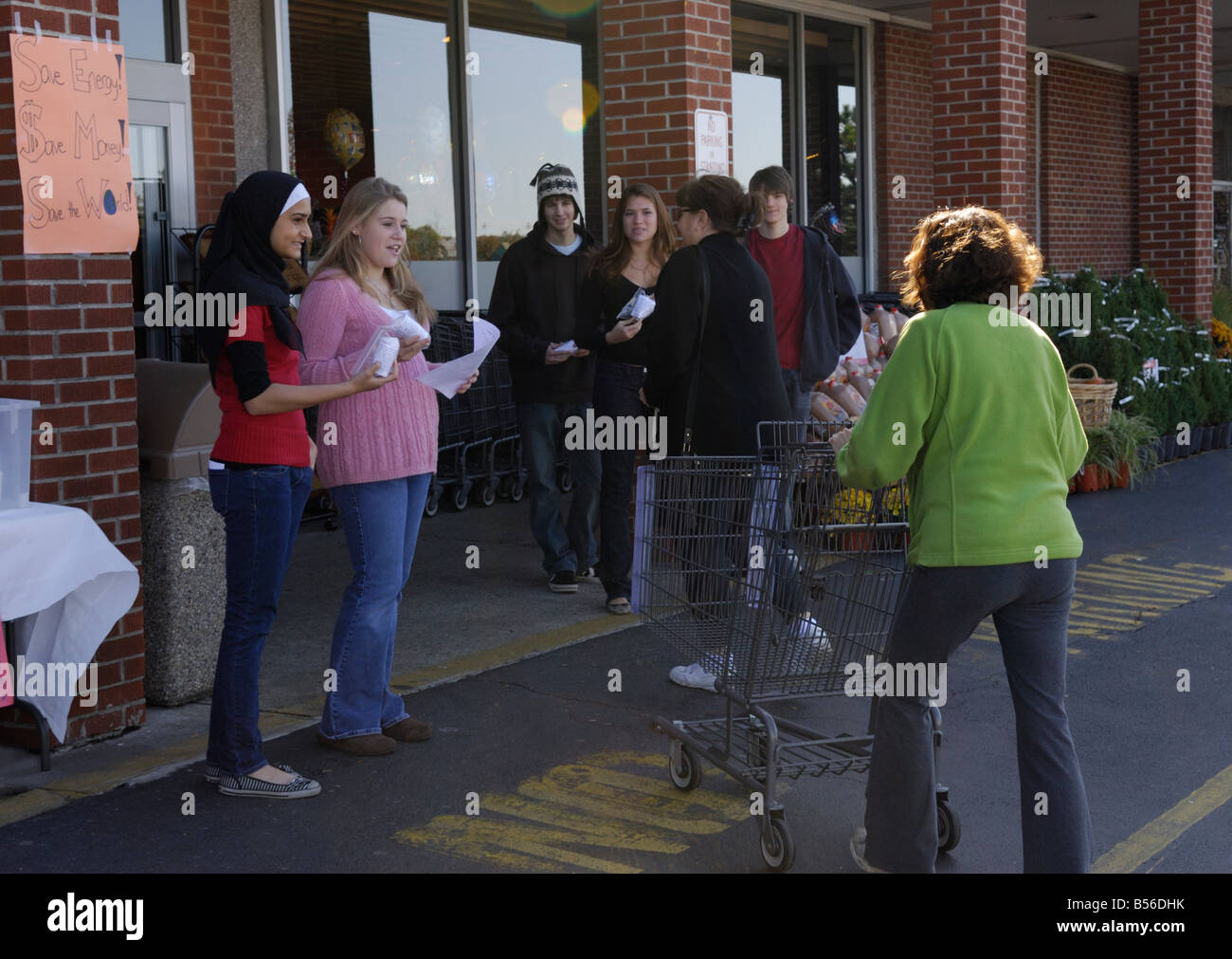 Teenage girls giving away free energy efficient light bulbs to people for an environmental community service project Stock Photo