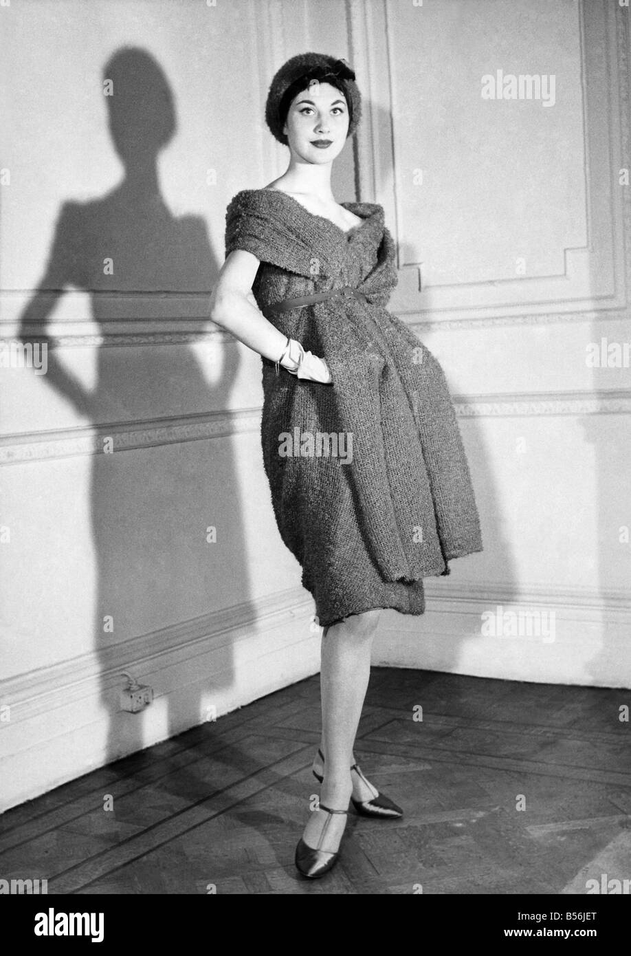 Fashion 1950's: That cuddly look again. John Cavanagh produces the cuddly look, too, with this empire line dress - Stock Image