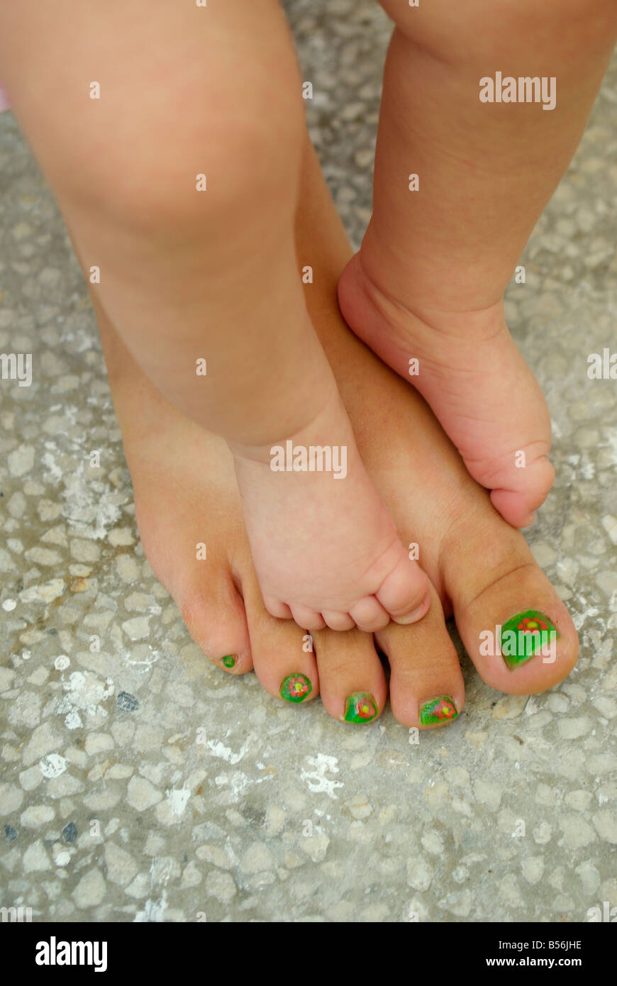 A child peduncle to leg of Mama - Stock Image