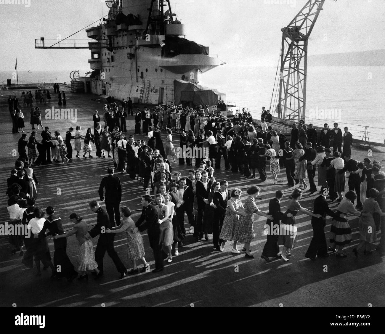 Dance on board H.M.S. Victorious. They are dancing on the deck of the aircraft-carrier H.M.S. Victorious, anchored - Stock Image