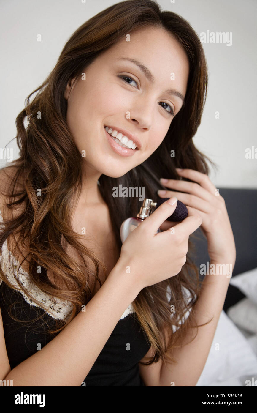 A woman spraying herself with perfume - Stock Image