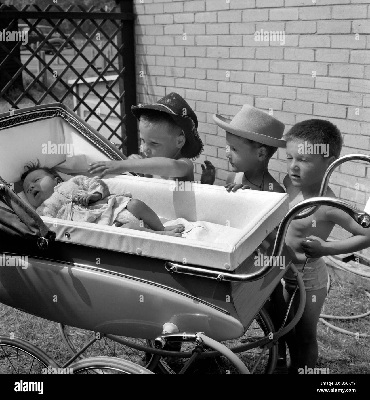 The three gloomy-faced triplet brothers all wearing cowboy hats leaning over the side of a pram in the garden of - Stock Image