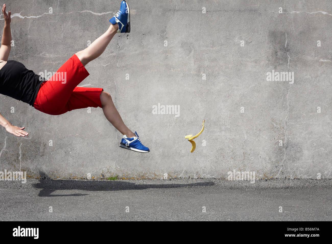 Woman falling on a banana skin - Stock Image