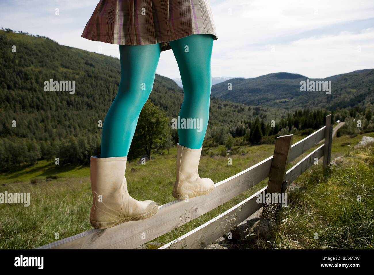 Woman walking on a wooden fence - Stock Image