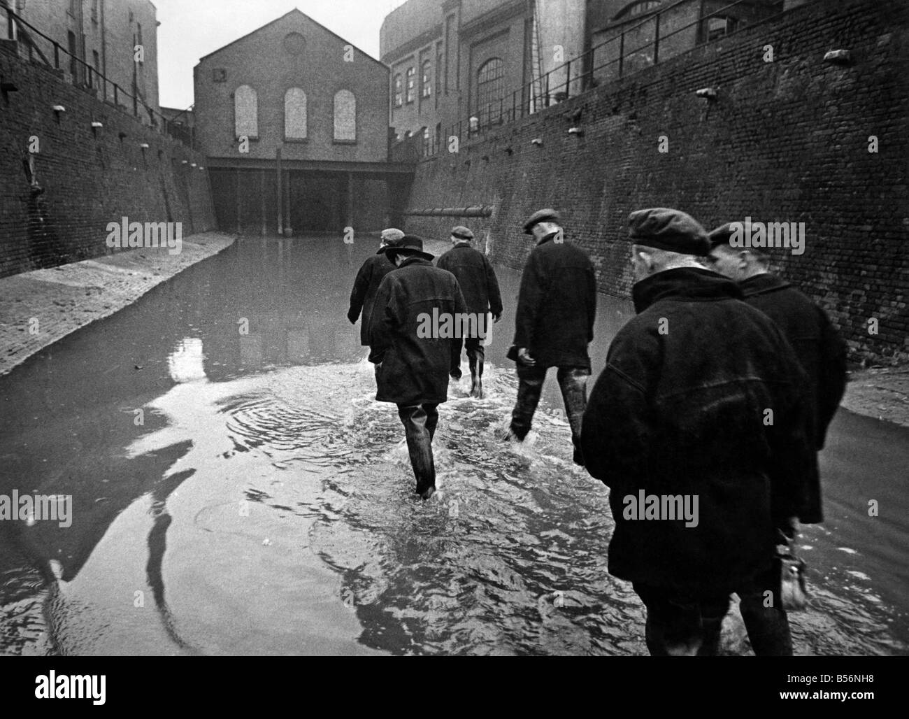 Edward Farmer's gang wade through the flowback from the Thames into the King's Scholars Pond sewer to inspect the Stock Photo