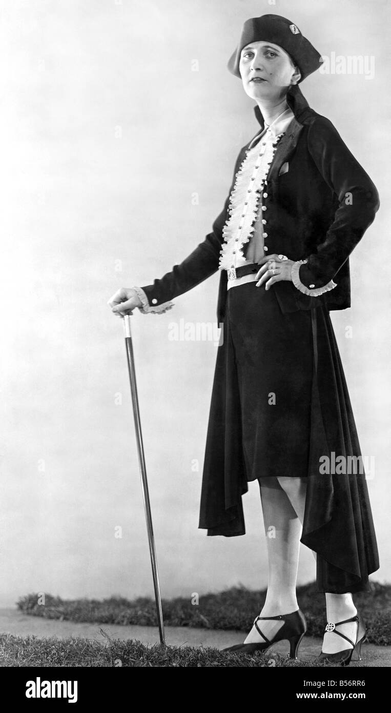 Woman wearing black jacket with skirt and long drape coat over with matching black hat. In one hand holding a staff - Stock Image