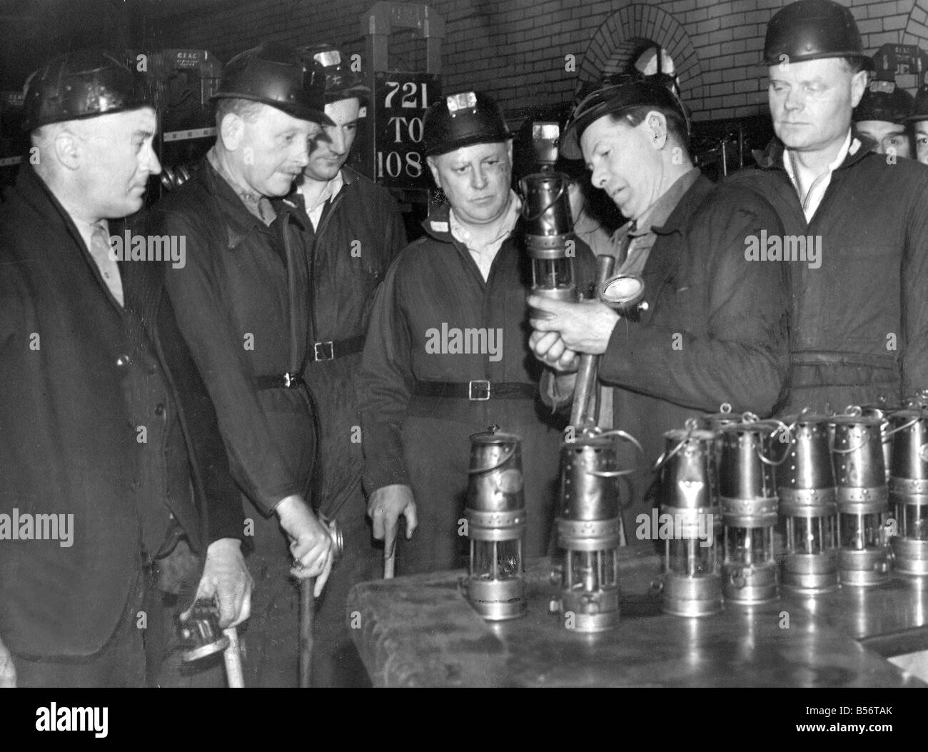Their lamps are checked by safety man James Harrison then they are frisked for inflammable materials before going - Stock Image