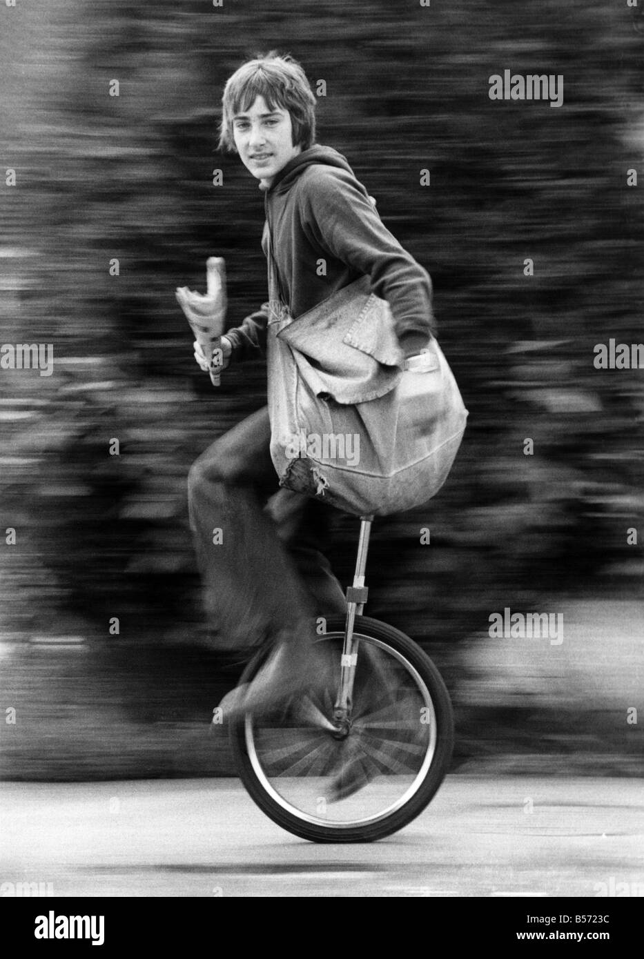 Newsboy Nigel Safe aged 14, knows what makes his paper round run smoothly- his unicycle. He can sort out the papers - Stock Image