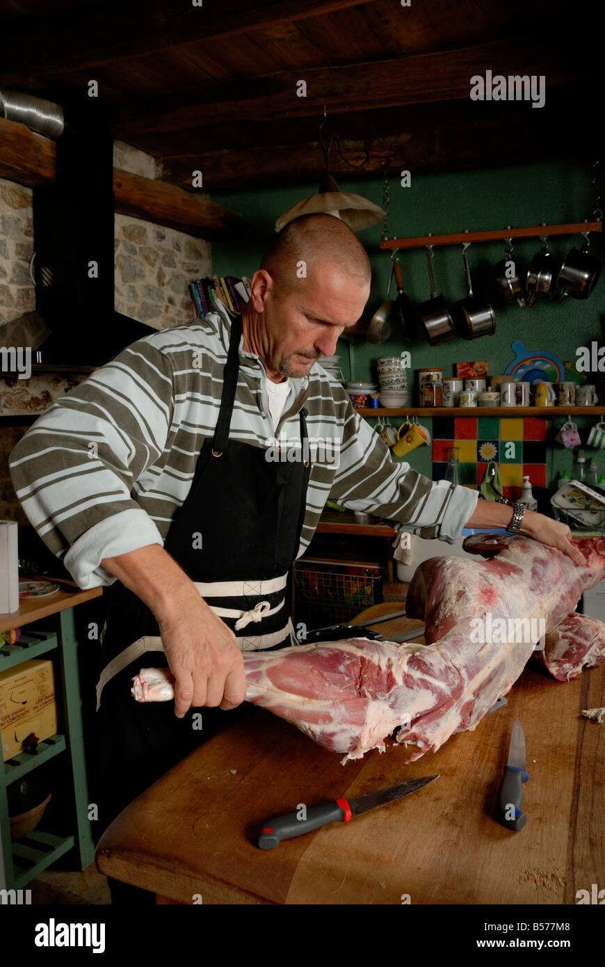 Stock photo of a man butchering a lamb - Stock Image