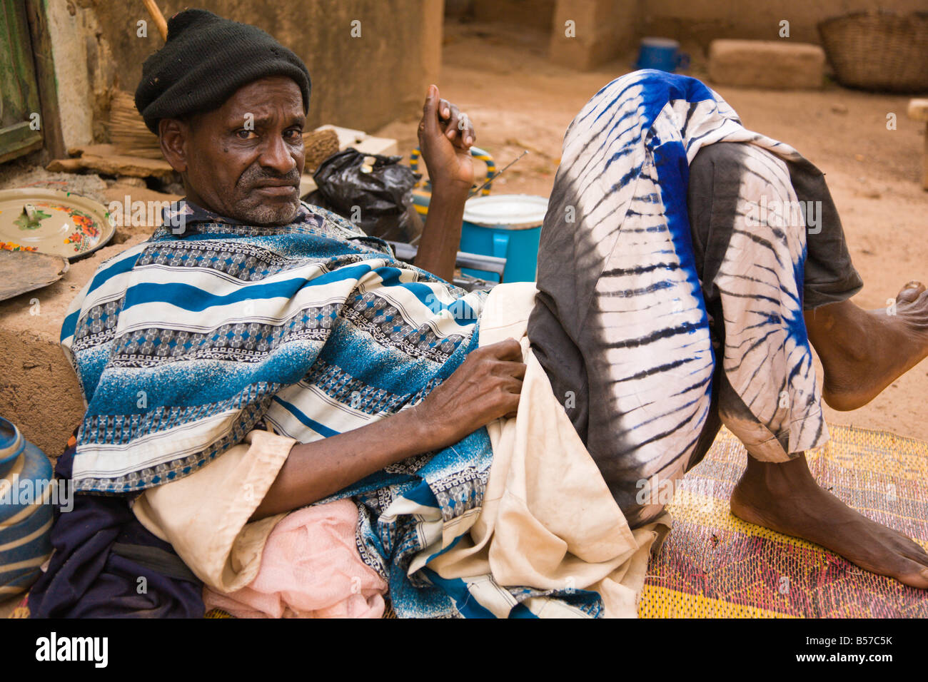 An elderly Fulani man relaxes against the steps of his house in Ouagadougou, Burkina Faso - Stock Image