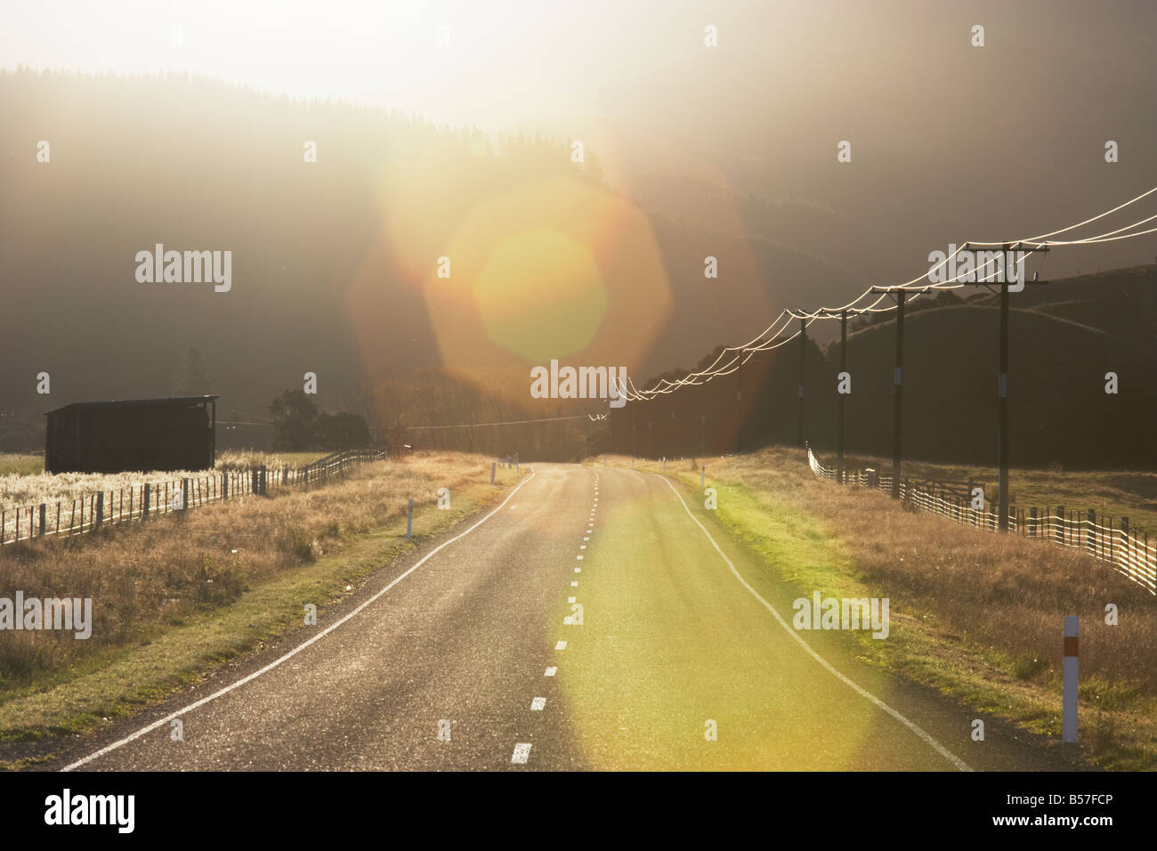 Road and telegraph wires leading into the sun and mountains Lewis Pass Christchurch and Canterbury South Island - Stock Image